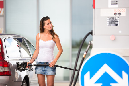scarce resources: Attractive, young woman refueling her car in a gas station, checking the amount of gas, disliking the price tag and the gas mileage of her engine