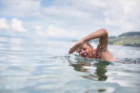swim: Senior hombre nadando en el Mar  Océano - disfrutando de la jubilación activa, divertirse, cuidar de sí mismo, mantenerse en forma