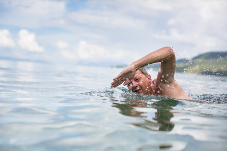 staying fit: Senior man swimming in the SeaOcean - enjoying active retirement, having fun, taking care of himself, staying fit