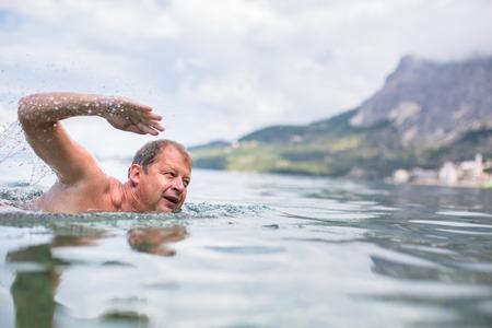 Senior man swimming in the SeaOcean - enjoying active retirement, having fun, taking care of himself, staying fit