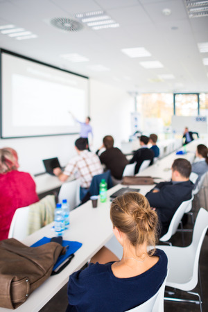 People listening to a presentation in a modern, bright meeting room (shallow DOF; color toned image) photo
