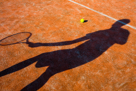 tennis shoe: Shadow of a tennis player in action on a tennis court (conceptual image with a tennis ball lying on the court and the shadow of the player positioned in a way he seems to be playing it) Stock Photo