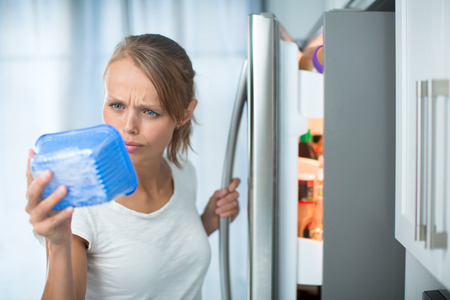 bad apple: Is this still fine? Pretty, young woman in her kitchen by the fridge, looking at the expiry date of a product she took from her fridge -