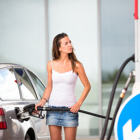 fueling: Attractive, young woman refueling her car in a gas station, checking the amount of gas, disliking the price tag and the gas mileage of her engine