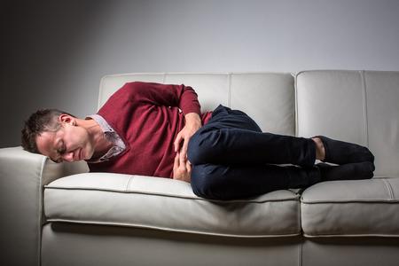 Junger Mann mit schweren Bauchschmerzen, die von der lähmenden Zustand der Zöliakie überwältigt  Morbus Crohn  strong Angst
