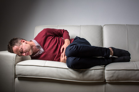 pain: Young man suffering from severe belly pain, being overwhelmed by the debilitating condition of celiac diseaseCrohns diseasestrong anxiety Stock Photo