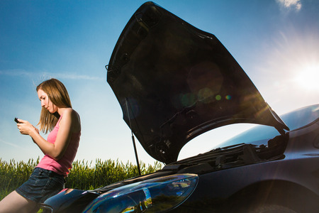assistance: Pretty, young woman calling the roadside serviceassistance after her car has broken down Stock Photo