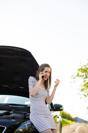 Pretty, young woman calling the roadside serviceassistance after her car has broken down photo