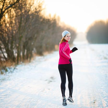 Winterlauf - Junge Frau läuft im Freien an einem kalten Wintertag Lizenzfreie Bilder