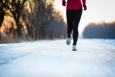 winter season: Winter running - Young woman running outdoors on a cold winter day