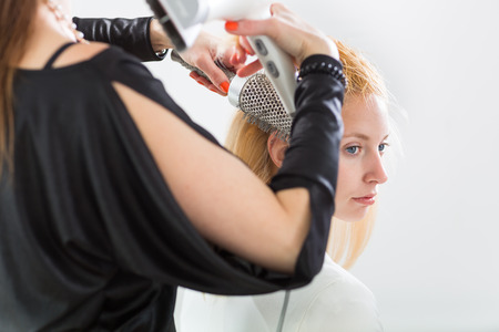 HairdresserHairstyle artist working on a young womans hair, giving it shape and volume photo
