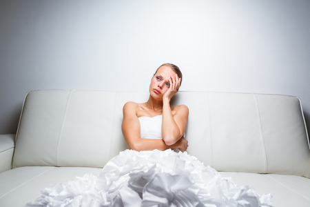 Sad bride crying sitting on a sofa, smitten, pondering, feeling low and depressed Imagens