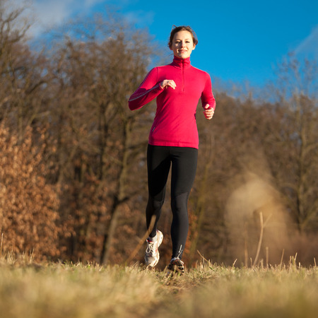 Young woman running outdoors on a lovely sunny winterfall day photo