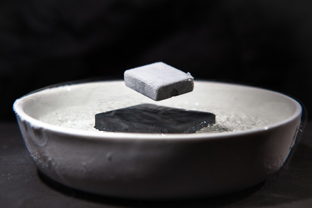 cooled: Physics in action - experiment with supraconductive materials, when cooled down by liquid nitrogen, these magnets are strong enough to make each other levitate Stock Photo