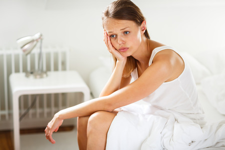 lacking: Pretty, young woman sitting on bed looking unhappy, depressed, feeling burnout, lacking motivation to get up and do what is expected  from her Stock Photo