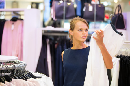 look in mirror: Beautiful young female shopper in a clothing store, chossing a blouset-shirtgarments (shallow DOF; color toned image) Stock Photo