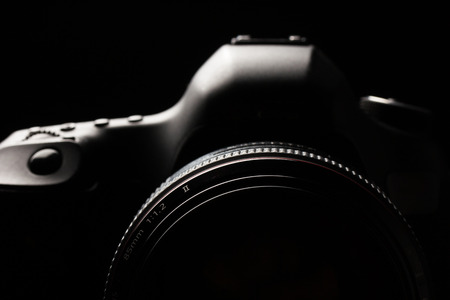 self service: Professional modern DSLR camera low key image - Modern DSLR camera with a very wide aperture lens on