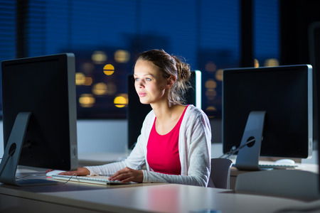 Pretty, young female college student using a desktop computerpc in a college library (shallow DOF; color toned image) Stock Photo