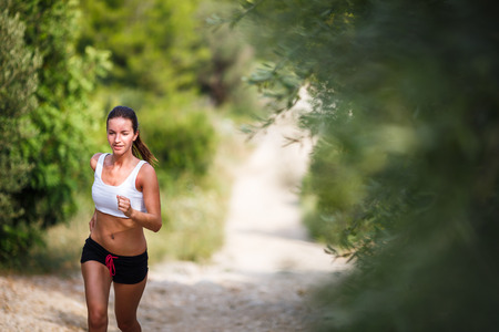 Beautiful young female runner on a forest path, on a lovely summer day photo