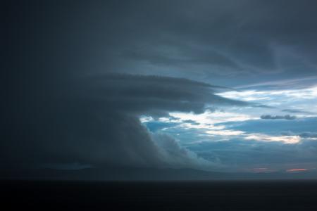 Gathering storm clouds in a vast landscape photo