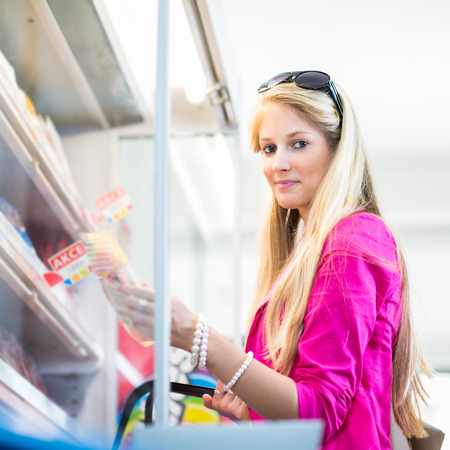 Beautiful young woman shopping in a grocery storesupermarket (color toned image) photo
