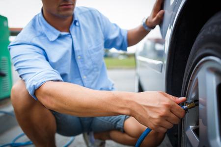 Treiber die Überprüfung des Luftdrucks und füllt Luft in den Reifen seines modernen Autos