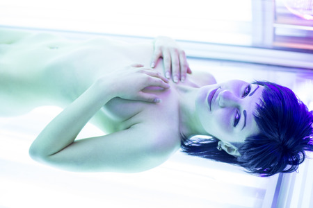 sunbed: Pretty, young woman tanning her skin in a modern solariumsunbed Stock Photo