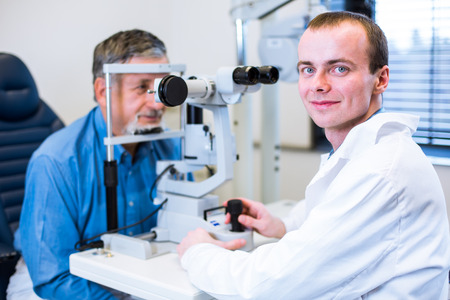 oap: Optometry concept - senior man having his eyes examined by an eye doctor (color toned image; shallow DOF)