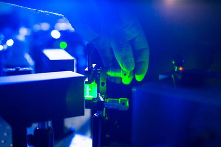 量子光学・ ラボでレーザー ビームを調整する研究者の手