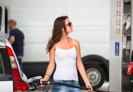 car gas: Attractive, young woman refueling her car in a gas station, checking the amount of gas, disliking the price tag and the gas mileage of her engine