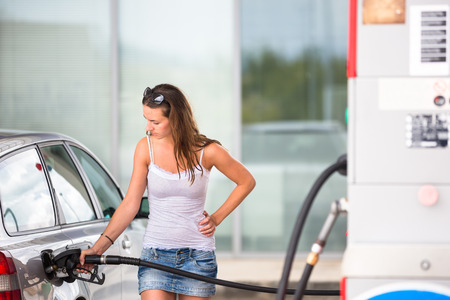 mileage: Attractive, young woman refueling her car in a gas station, checking the amount of gas, disliking the price tag and the gas mileage of her engine
