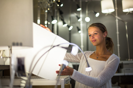 Pretty, young woman choosing the right light for her apartment in a modern home furnishings store (color toned image; shallow DOF) photo