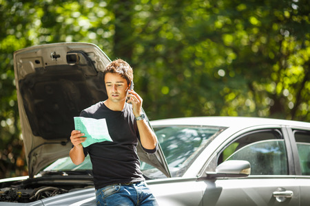 company: Handsome young man calling for assistance with his car broken down by the roadside