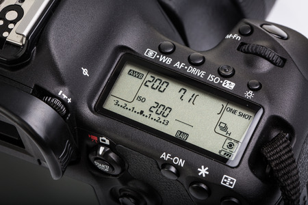 Professional modern DSLR camera - detail of the top LCD with settings - shutter speed, aperture, ISO, AF mode, battery info, RAW format indication Stock Photo