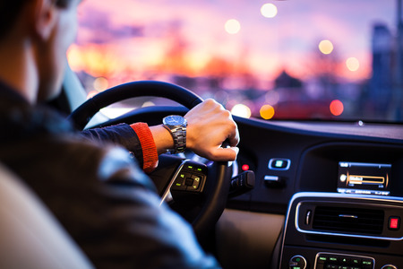 Driving a car at night -man driving his modern car at night in a city (shallow DOF; color toned image) Archivio Fotografico