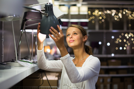 Pretty, young woman choosing the right lamp for her apartment in a modern home furnishings store (color toned image; shallow DOF) photo