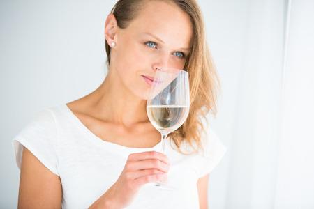 sorbo: Hermosa mujer joven con un vaso de vino, oliendo la bebida encantadora, saboreando cada sorbo (DOF, imagen en color entonado)