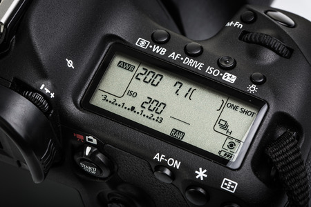 eos: Professional modern DSLR camera - detail of the top LCD with settings - shutter speed, aperture, ISO, AF mode, battery info, RAW format indication Stock Photo
