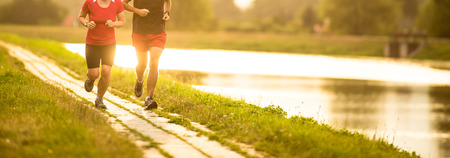Couple running outdoors, at sunset, by a river, staying active and fit Imagens