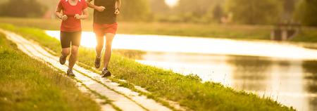 Paar läuft im Freien bei Sonnenuntergang an einem Fluss, aktiv zu bleiben und fit