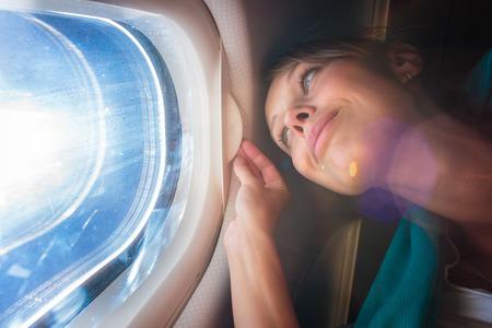 gente aeropuerto: Feliz, hembra avión pasajero disfruta de la vista desde la ventana cabon sobre el cielo azul (DOF; bengala intencional) Foto de archivo