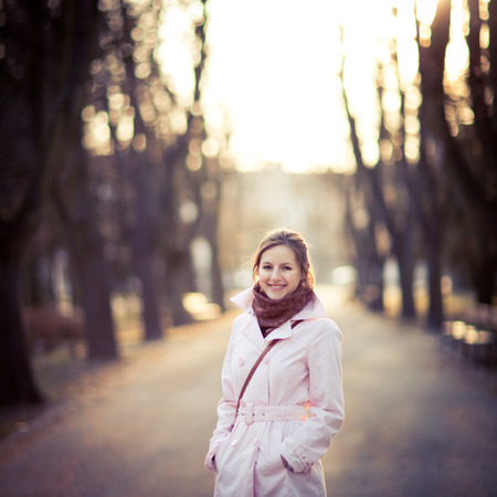 Seasonal portrait of a young woman outdoors in a park standing in an alley lit by spring evening sunshine (color toned image, shallow depth of field) photo