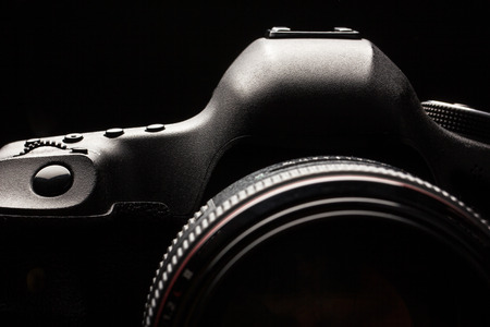 snap: Professional modern DSLR camera low key image - Modern DSLR camera with a very wide aperture lens on