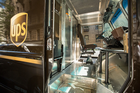 parcels: MANHATTAN, NYC, UNITED STATES - SEPTEMBER 15, 2014: UPS delivery truck cabin, driver out for delivery