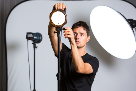 pro: Young pro photographer in his studio setting up lights for the upcoming photoshoot