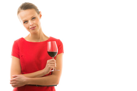 Elegant young woman in a red dress, having a glass of red wine isolated on white background photo