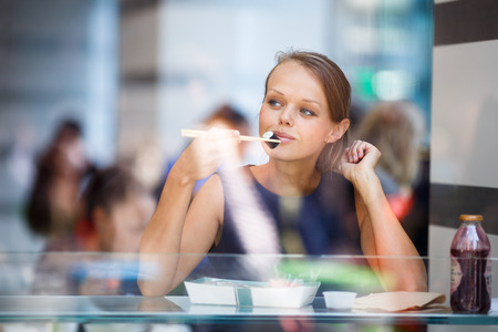 womna: Pretty, young womna eating sushi in a restaurant, haivng her lunch break, enjoying the food, pausing for a while from her busy corporateoffice life (color toned image) Stock Photo
