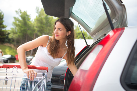 Beautiful young woman shopping in a grocery storesupermarket (color toned image), putting the groceries into her car in the parking lot, looking around photo