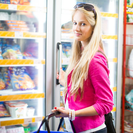 produce departments: Beautiful young woman shopping in a grocery storesupermarket (color toned image)