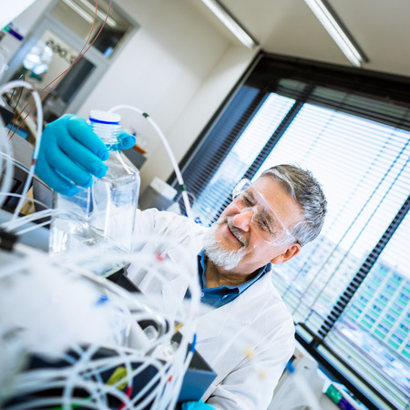 scientific equipment: Senior male researcher carrying out scientific research in a lab Stock Photo
